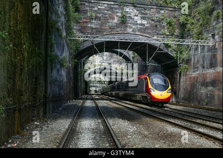 A Virgin Pendolino leaves Liverpool Lime Street through the alternate light and shade created by the caverns. - Stock Photo