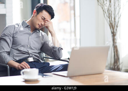 Tired young man rubbing eyes in office - Stock Photo