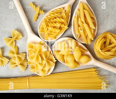 Various types of pasta in wooden spoons on stone table, top view - Stock Photo