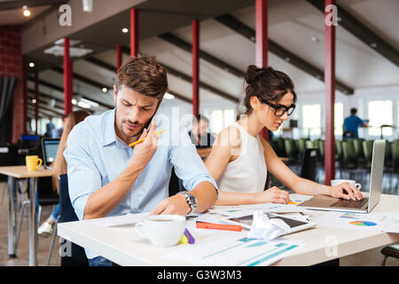 Focused young businessman and businesswoman sitting and working in office - Stock Photo