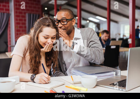 Happy young business people working together and laughing in office - Stock Photo