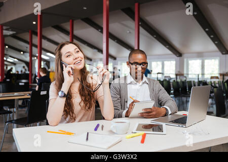 Smiling young businesswoman talking on mobile phone while her colleague is working in office - Stock Photo