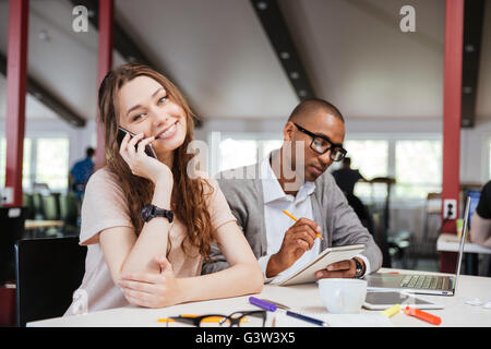 Cheerful beautiful young business woman talking on cell phone and working with serious african man in office - Stock Photo