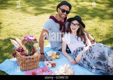 Portrait of smiling beautiful young couple having picnic on the lawn in park - Stock Photo