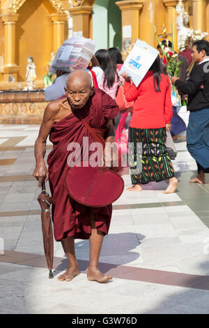 An old monk bent with age who is going to perform his devotions at the Paya Shwedagon, in Yangon (Myanmar). - Stock Photo