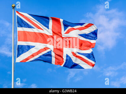 Union Jack flag of United Kingdom of Great Britain and Northern Ireland, flying on a pole against blue sky. - Stock Photo