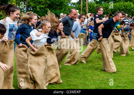 Teenagers and Adults Race In A Traditional Sack Race At The Medieval Fair Of Abinger, Surrey, UK - Stock Photo