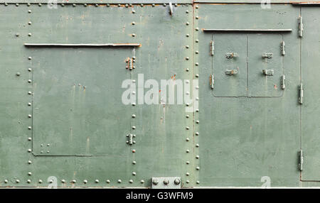 Abstract green industrial metal background texture with manholes, bolts and rivets, details of Russian armored train - Stock Photo