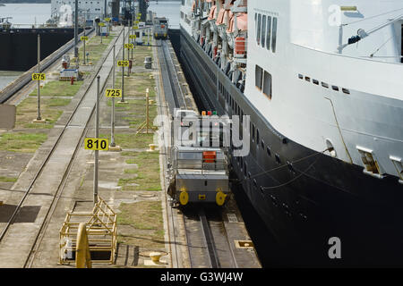 Electric mules steering large cruise ship at the first locks on Panama Canal, Miraflores Locks, Pacific Ocean - Stock Photo