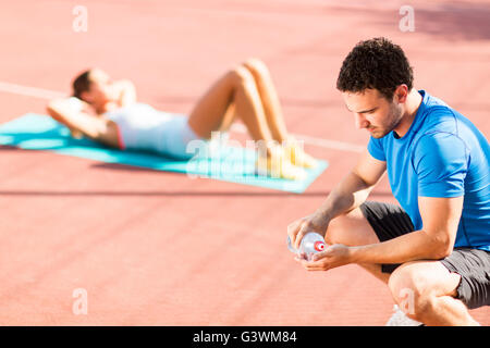 Woman training with personal trainer outdoor - Stock Photo
