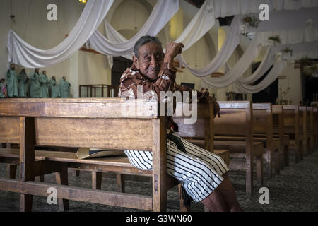 A devoted waits sitting in one of the pews of the church in Santiago Atitlan - Stock Photo