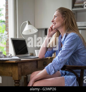 Woman having a morning phone call in her home office - Stock Photo