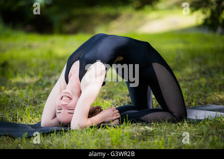 Portrait of beautiful smiling sporty fit blond young woman doing bikram yoga backbend on summer day, Natarajasana, - Stock Photo