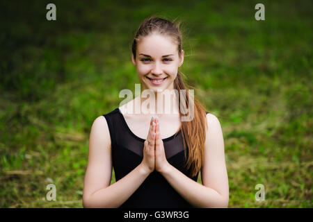 Young yoga teacher practicing outdoors in a park over green grass - Stock Photo