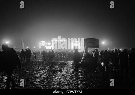 thousands of people leaving the main stage at download music festival late at night in mud after last band - Stock Photo
