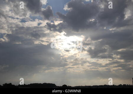 Beautiful rays of sunlight pierce the through the dark clouds creating radiant beams shooting down to earth in all - Stock Photo