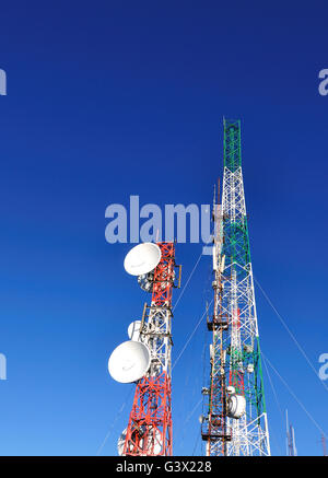 Satellite and communication towers against blue sky, vertical image. - Stock Photo