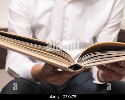 Handsome man reading an old book on a sofa - Stock Photo