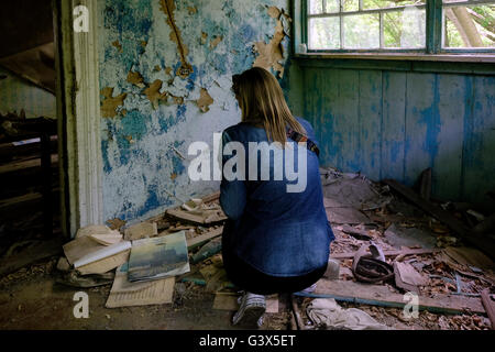A visitor inside an abandoned house in the deserted village of Zalissya located inside the Chernobyl Exclusion Zone - Stock Photo