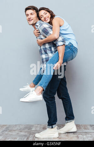 Young couple enjoying piggyback ride isolated on gray background - Stock Photo