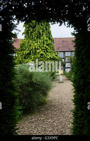 Cottage through a hedge. Ashton Under Hill, Wychavon district, Worcestershire, England - Stock Photo