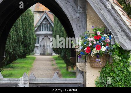 Flower basket on St Marys church lychgate. Hambleden, Buckinghamshire, England - Stock Photo