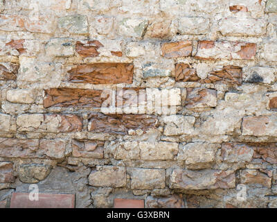 Old damaged red brick wall with plaster texture background - Stock Photo