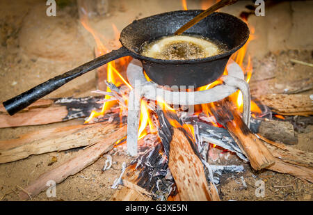 Cooking Rice bread  on firewood traditionally in the rural village of Nepal. - Stock Photo