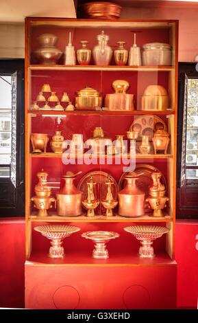 Copper utensils that are used in Thakali Vanchha Ghar or Restaurants kept on a wooden rack in Pokhara,Nepal. - Stock Photo