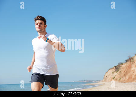 Attractive young man in white t-shirt and black shorts running along the beach - Stock Photo