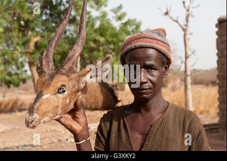 MALI , traditional hunter with Deere head in village Dialkoro / MALI Jaeger im Dorf Dialkoro - Stock Photo