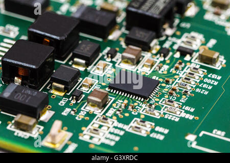 Printed circuit board with ICs, chip capacitors, and chip resistors. - Stock Photo