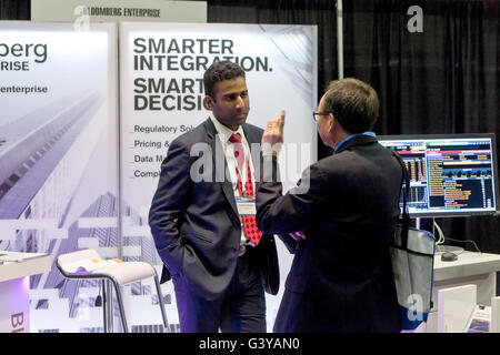 Businessmen discussing business and chatting in front of Bloomberg booth at a business expo - USA - Stock Photo