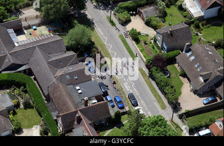 aerial view of a Primary school with supervised children crossing the road, UK - Stock Photo
