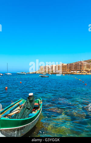 Fishing boat moored in Marsalforn Bay and panorama of the most popular and largest summer resort - Marsalforn, Gozo, - Stock Photo
