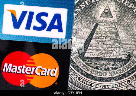 Tambov, Russian Federation - April 02, 2016 Visa and MasterCard logo on credit cards on one dollar bill with pyramid - Stock Photo