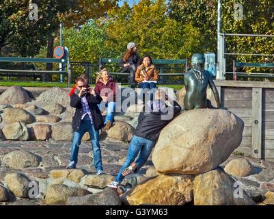 Copenhagen, Denmark:  Tourists playing around The Little Mermaid statue, waterside in Langelinie promenade. - Stock Photo