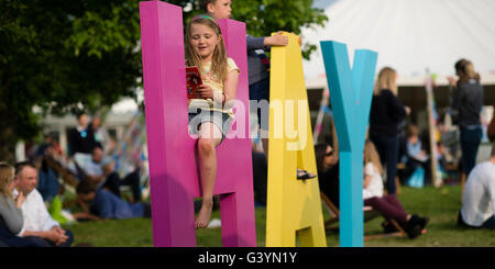People visiting attending enjoying themselves with one of the big signs at  the Hay Festival of literature and the - Stock Photo