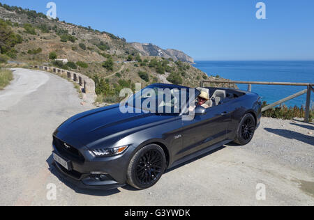 Woman driving Ford Mustang 5 Litre V8 convertable with open top.