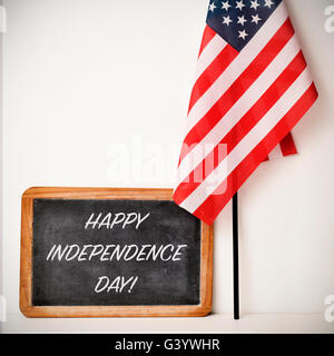 a wooden-framed chalkboard with the text happy independence day written in it and a flag of the United States, on - Stock Photo