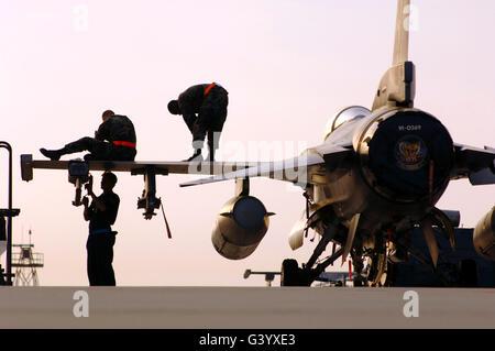 rew chiefs prepare an F-16 Fighting Falcon for take-off. - Stock Photo