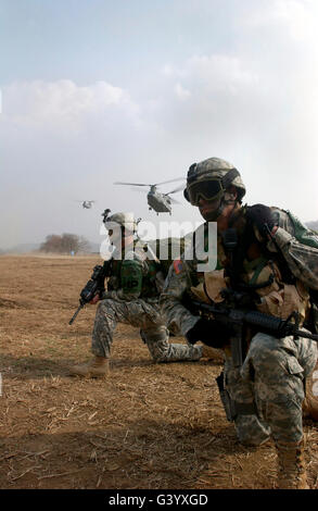 U.S. Army Sergeants secure a helicopter landing zone for a CH-47 Chinook. - Stock Photo