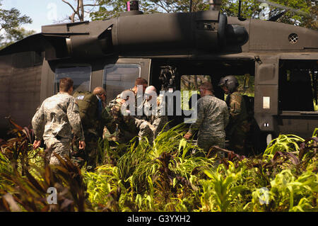 U.S. Army Soldiers load a patient onto a UH-60 Black Hawk helicopter. - Stock Photo