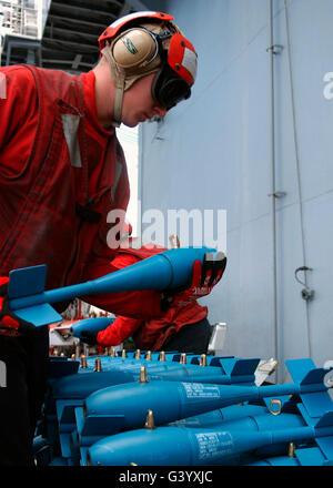 U.S. Navy Aviation Ordnanceman prepares inert training bombs. - Stock Photo