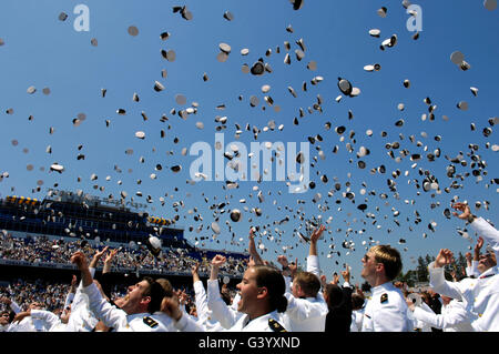 Graduates of the U.S. Naval Academy throw their hats into the air. - Stock Photo