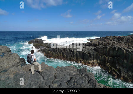 Hiker is standing on the rocky coast of El Hierro - Stock Photo