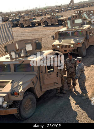 U.S. Army soldier speaks with Iraqi Army Soldiers prior to them driving M1114 HMMWVs. - Stock Photo