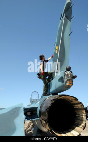 A technician performs post flight maintenance on a JASDF F-2 fighter aircraft. - Stock Photo