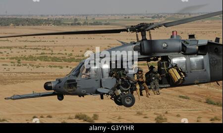 A U.S. Air Force HH-60 Pavehawk flies over the Iraqi landscape. - Stock Photo