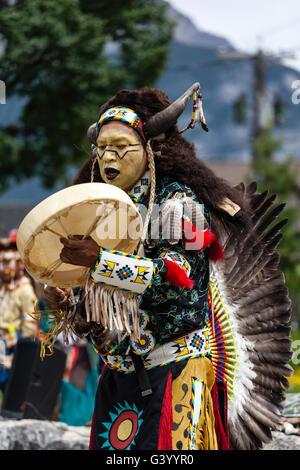 BANFF, CANADA- JUL 3, 2014: A native Blackfoot indian chief wearing a split-horn bonnet dances at a performance - Stock Photo